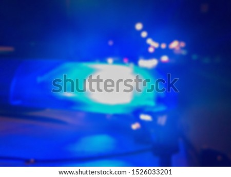 Abstract blurry image. Blue police car lights on the background of the night road, crime scene. Car accident concept.