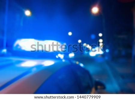Abstract blurry image. Police car lights on the background of the night road, crime scene. Car accident concept.