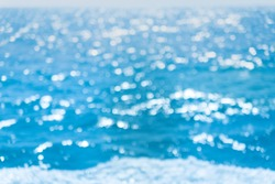 Abstract bokeh background from summer blue sea water at the beach. Lights on sea background. The blur cool sea background. Relaxing outdoors vacation concept.