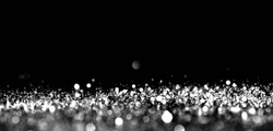 Abstract bokeh silver light glitter on black background. Blurred circle black and white sparkle magic background.