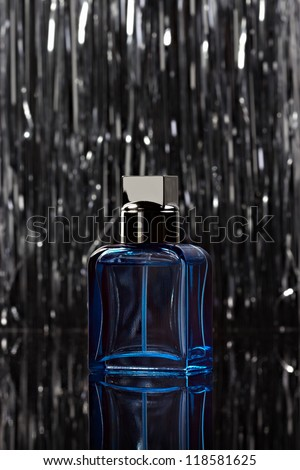 Abstract bottle of perfume over abstract background. Low key.