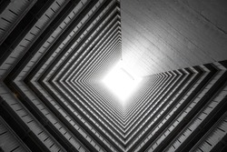 Abstract building facade concrete void or tunnel with natural light in the end in twist view/ architecture design / abstract concept / background texture