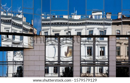 abstract building facades with vintage  buildings reflecting in modern glas facade and creating distortion of lines #1579579129