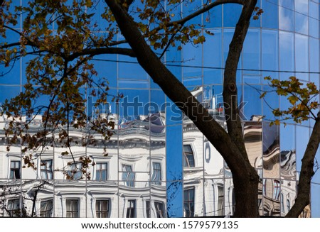 abstract building facades with vintage  buildings reflecting in modern glas facade and creating distortion of lines #1579579135