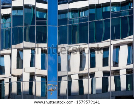 abstract building facades with vintage  buildings reflecting in modern glas facade and creating distortion of lines #1579579141