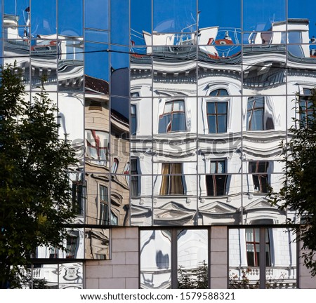 abstract building facades with vintage  buildings reflecting in modern glas facade and creating distortion of lines #1579588321