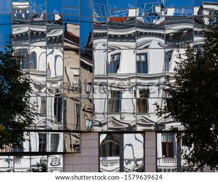 abstract building facades with vintage  buildings reflecting in modern glas facade and creating distortion of lines #1579639624