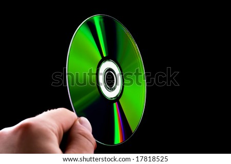 abstract cd dvd blue-ray disk in hand isolated on black