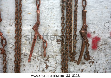 Abstract chain hanging over a weathered piece of wood or fence