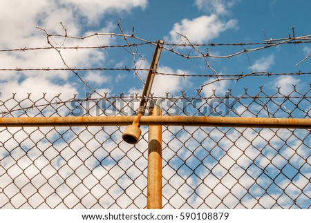 Abstract chain link fence with barbed wire. Broken chain steel fence with barbed wire and branches. Branches and roots on steel gate frame. Industrial art and design. Abstract sky colorful background. #590108879