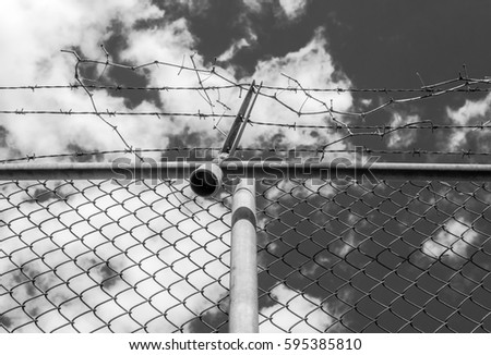 Abstract chain link fence with barbed wire. Broken chain steel fence with barbed wire and branches. Branches and roots on steel gate frame. Industrial art and design. Abstract sky colorful background. #595385810