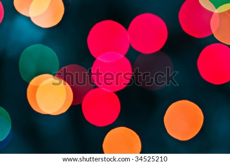 Abstract Christmas bokeh lights of red, green and gold against a black background.