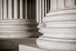Abstract close-up of the neoclassical white marble fluted columns at the entrance to the US Supreme Court Building in Washington DC, USA