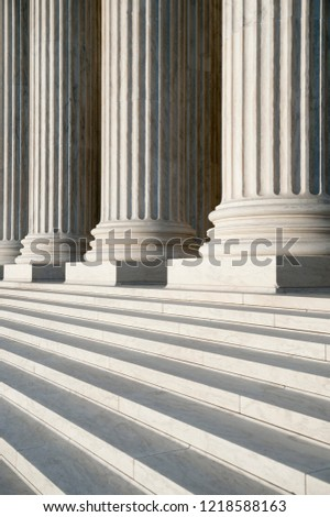 Abstract close-up of the neoclassical white marble fluted columns with steps at the entrance to the US Supreme Court Building in Washington DC