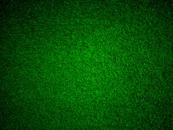 Abstract close up top view green color of artificial grass background texture made width dark border filters.