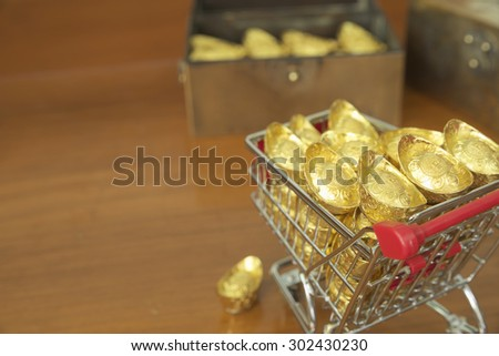 Abstract closeup concept of gold treasuring into chest by pushcart with a gold drop on its\' side. The chinese words are crafted into gold with meaning of good fortune, best of luck, and good health.