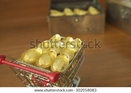 Abstract closeup concept of gold treasuring into treasure chest by pushcart. The chinese words are crafted into gold with meaning of good fortune, best of luck, and good health.