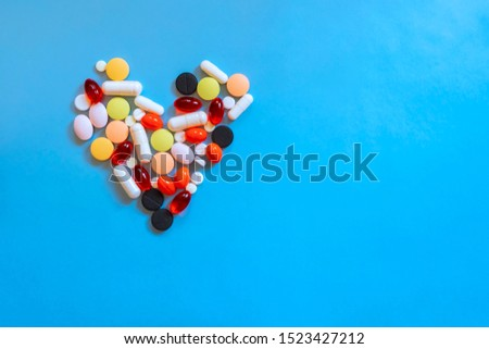 Abstract closeup of colorful heap of pills in heart shape on blue background. Health care, medical concept. Love concept. Drug concept. Healthcare concept.