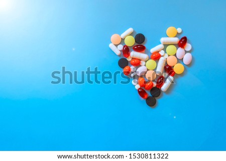 Abstract closeup of colorful heap of pills in heart shape on blue background. Health care, medical concept. Love concept. Drug concept. Healthcare concept. #1530811322