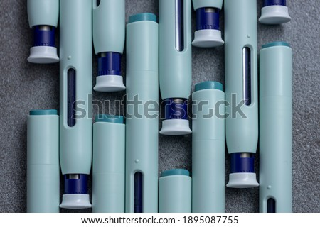 Abstract closeup of organized syringe self application pens on rustic gray kitchen counter background. Studio medical equipment still life concept with auto-injector disposable devices.