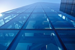 Abstract closeup of the glass-clad facade of a modern building covered in reflective plate glass