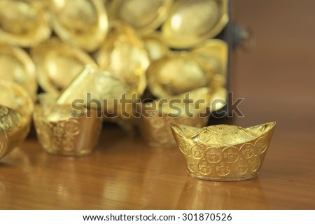 Abstract closeup of tilted treasure box with chinese style gold bar leaking out. The chinese words are crafted into gold with meaning of good fortune, best of luck, and good health.