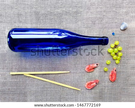 Abstract collage for poster, picture, advertisement in a bar. Blue riesling wine bottle, shrimp, grape brush, sushi sticks on a gray canvas background.