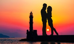 Abstract collage of silhouette of romantic lovers with lighthouse on a background.  Lighthouse of Chania at summer sunset , Crete , Greece. Love and travel concept