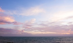 abstract color of the pinky sky and soft warm color clouds in dawn time, sunrise morning over seacoast. skies covered by romantic cirrus clouds, nature landscape background of Samui island in Thailand