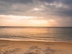abstract color of yellow beach in golden sunset at the beach. dramatic gray cloudy sky above seawater. sunlight shines through dark clouds. sun rays beam shine on water surface. beautiful panoramic