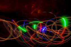 Abstract colored lines on a dark background. Red and green lines.
