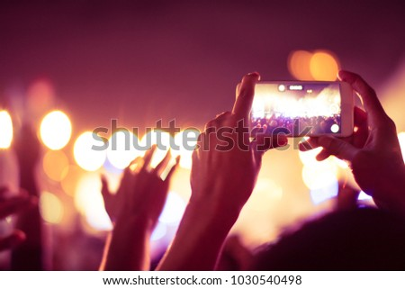 abstract colorful background of hand holding smart phone to taking memories by capture image photo and record video of lighting and people crowded in concert music event.using camera mobile concept.