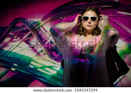 Abstract colourful image is projected on a young woman in sunglasses.