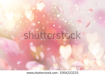 Abstract composition for Women's Day. Pink flower petals flying with hearts symbols, defocused background with lots of copy space.