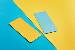 abstract composition of 2 design cards, comparison of two yellow and blue colored cards on a two-color paper background