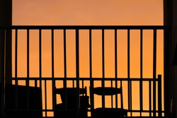 Abstract composition of metallic balcony black fence and chairs silhouettes in orange sunset sky background with copy space