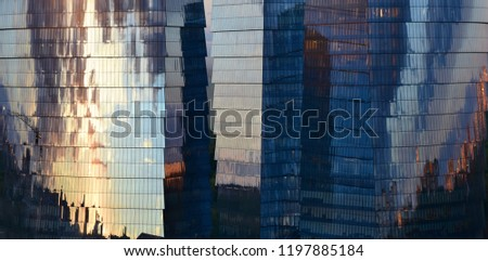 Abstract composition. Urban environment.  Three glass office skyscrapers in which the evening sky reflects.  #1197885184