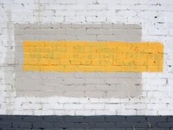 Abstract composition with a yellow horizontal strip, depicted on a painted brick wall. Background structure.