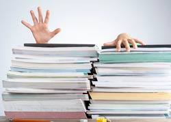 Abstract concept image showing a young student behind a large pile of test prep books on a study desk. An overwhelming load. The kid is trying to escape by climbing onto the pile as if she is drowning