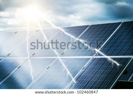 abstract concept of power plant using renewable solar energy with abstract storm and sun - stock photo