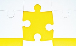 Abstract conceptual background with incomplete jigsaw puzzle. Symbol of association and connection, business strategy, completing, team support and help concept. White puzzles lie on yellow background