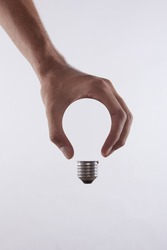 abstract conceptual image of a male's hand holding a light bulb shape