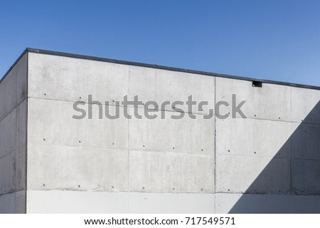 Abstract concrete interior, corner of grungy walls under blue sky #717549571