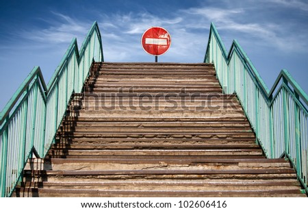 Abstract concrete structure with footsteps and prohibiting red No Entry sign at the end
