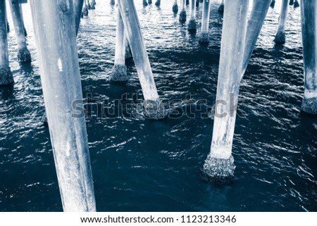Abstract construction detail of Santa Monica Pier in Pacific Ocean, Los Angeles, California, USA. Many large concrete pillars grown around with shells carry also famous amusement park.