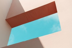 Abstract contemporary architecture fragment, empty window in pink painted concrete wall with blue sky outside