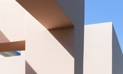 Abstract contemporary architecture photo background, niches in pink painted concrete walls are under blue sky