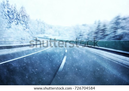 Abstract dangerous fast highway winter driving. Snowy conditions on the road. Motion blur visualizes the speed and dynamics. #726704584