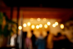 Abstract defocused background. Blurred people silhouettes and defocused lights in cafe.
