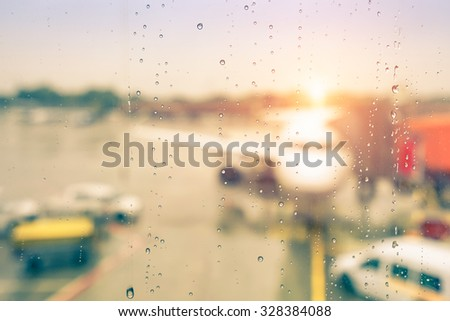 Abstract defocused bokeh of airplane at airport gate with sun coming out after the rain - Modern travel concept and wander lifestyle at sunset - Focus on raindrops with warm vintage filtered look
